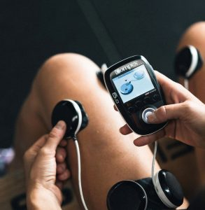 Athletic Recovery Centre | Woman holding compex machine